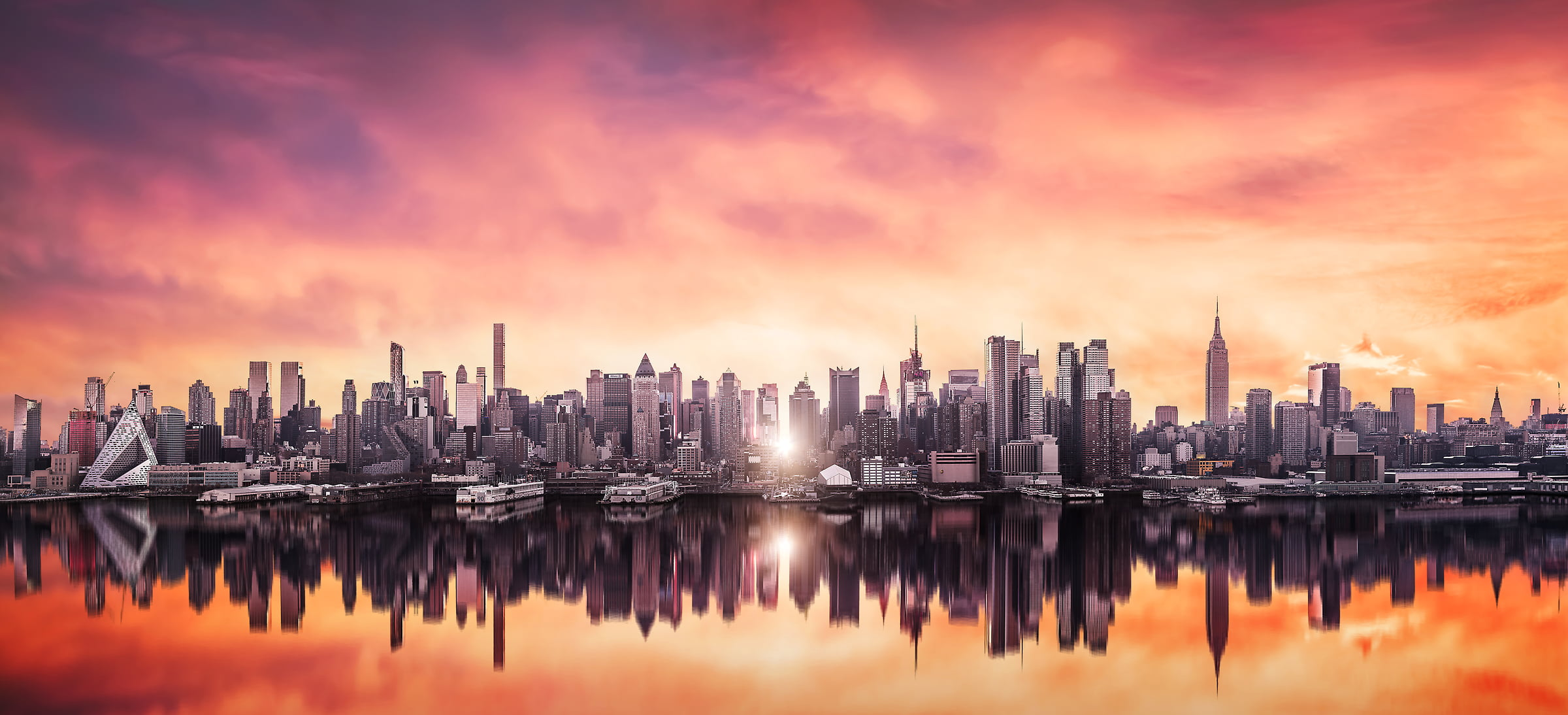 A very high definition cityscape VAST photo of Manhattanhenge sunrise among the Midtown Manhattan city skyline skyscrapers; created in New York City by Dan Piech