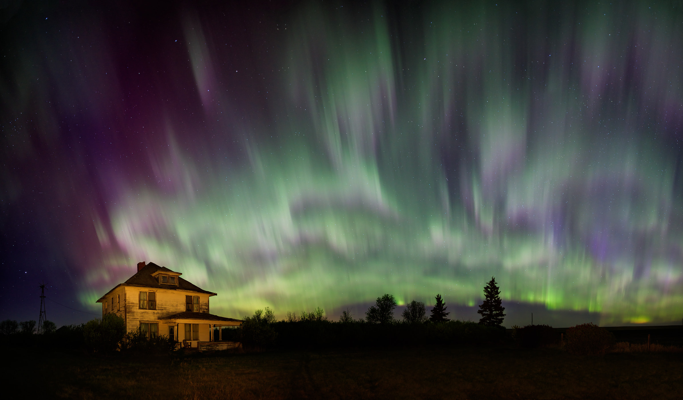 A very high resolution, large-format VAST photo of an eerie creepy abandoned house under the Aurora Borealis Northern Lights; fine art landscape photo created by Scott Dimond in Alberta, Canada