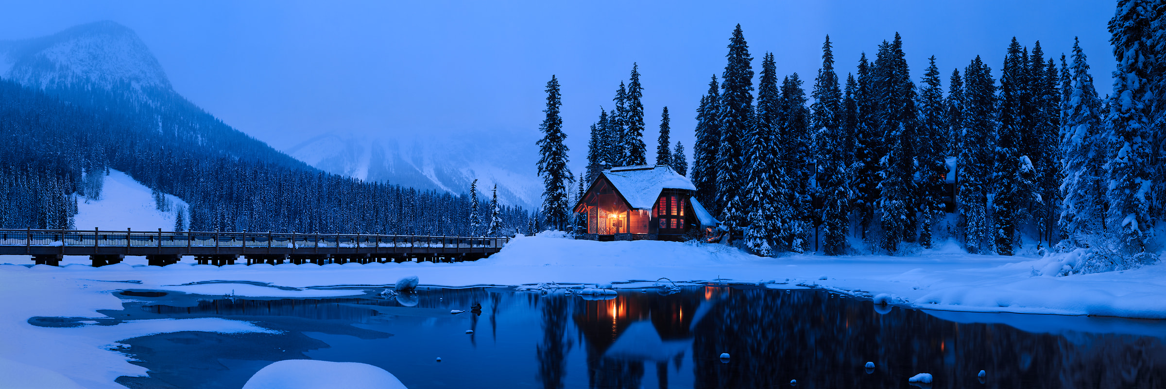 690 megapixels! A very high resolution, large-format VAST photo of a cozy winter scene with a snow covered forest, icy lake, a warm ski cabin in the woods, and snowy mountains; large-format photo print created at twilight by Scott Dimond in Yoho National Park, British Columbia, Canada