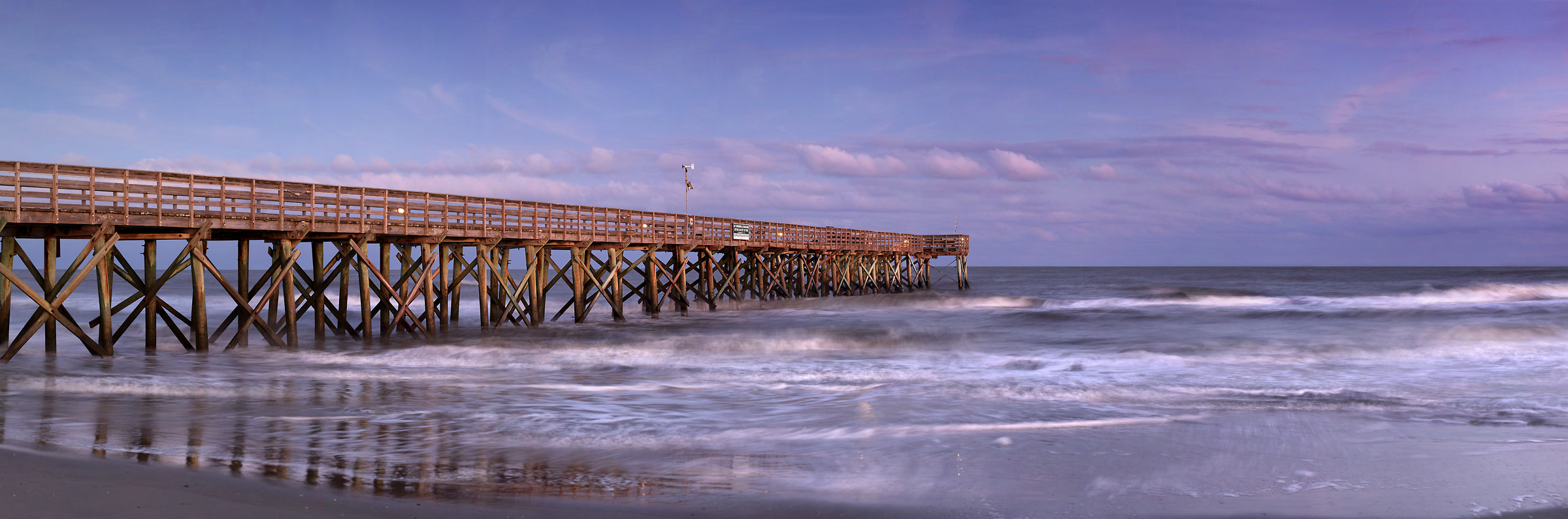 372 megapixels! A very high resolution, large-format VAST photo print of a beach with a pier going out into the ocean at sunset; photograph created by Phil Crawshay in Isle of Palms, South Carolina